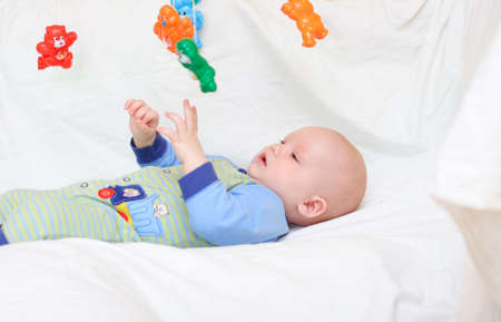 Baby playing with toys. Little boy touching the toys by finger photo