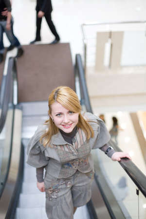 Pretty girl standing on escalator and moving up photo