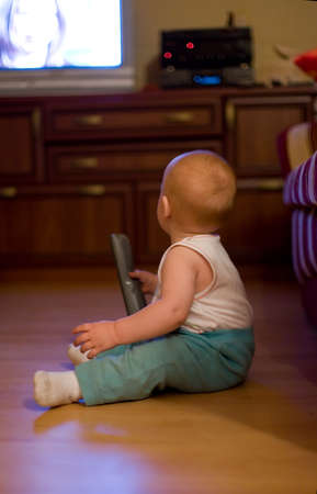 Cute little boy sit on hardwood floor, hold remote control and watching TV at home photo