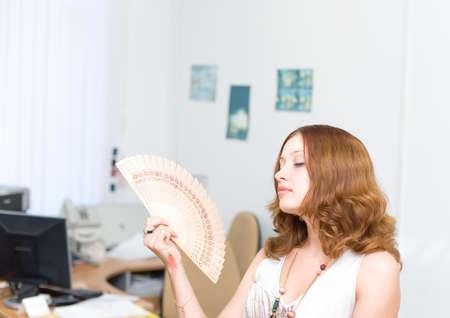 Girl in office brush away face by fan photo