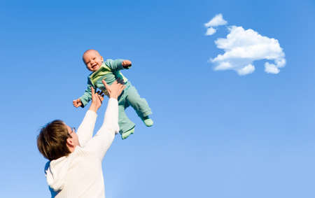 A father throwing his son in the air and catching him photo