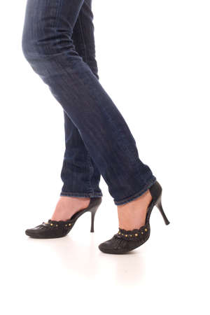 Woman legs dressed in jeans and black shoes walk forward over white background photo