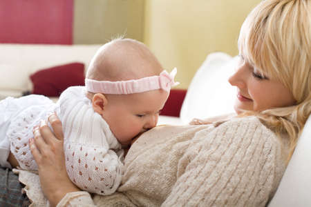 breast girl: Mother breast feeding her baby girl at home Stock Photo