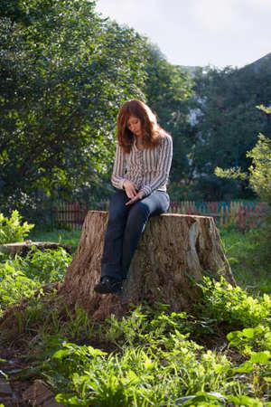 friendless: Young sad melancholic woman sit on big stub at sunlight day