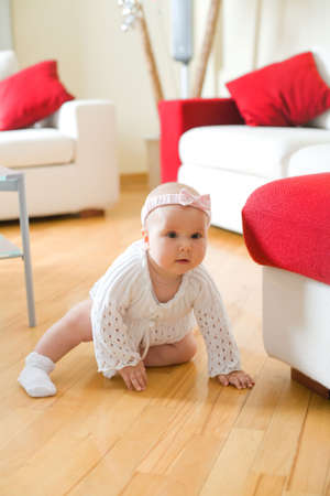 eye pad: Happy eight month old baby girl crawling on a hardwood floor in living room