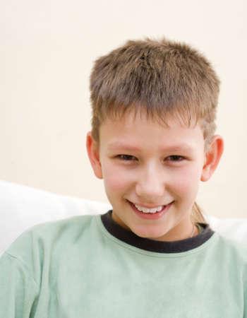 Smiling teenager sit on white sofa photo