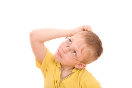 Boy look up and scratches his head in puzzlement or confusion, as if pondering a deep question. Over white background. Stock Photo