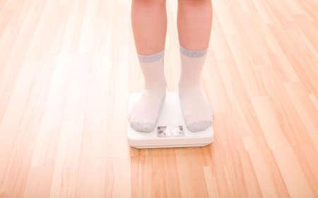 Boy measures weight on floor scales. Legs in socks standing at floor scales om hardwood floor in living room. photo