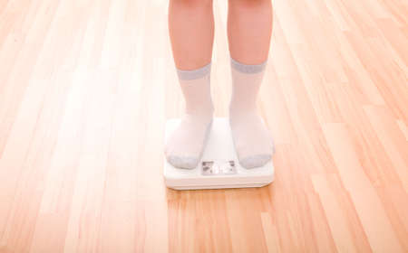 weigher: Boy measures weight on floor scales. Legs in socks standing at floor scales om hardwood floor in living room. Stock Photo