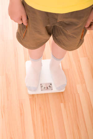 obese child: Boy measures weight on floor scales. Legs in shorts and socks standing at floor scales on hardwood floor in living room. View from above.