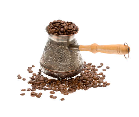 cezve: Cezve with freshly roasted coffee beans over white background. Focus on cezve