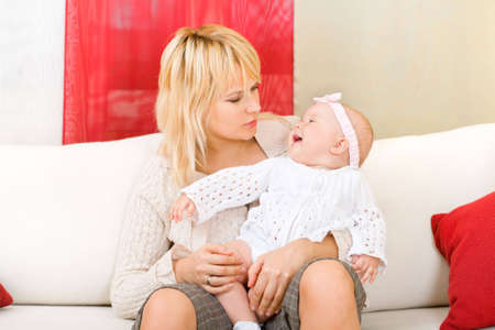 Mother seated on white sofa hold her baby girl photo