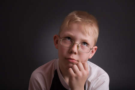 puzzlement: Boy look up and prop his head by hand in puzzlement as if pondering a deep question. Over grey background.