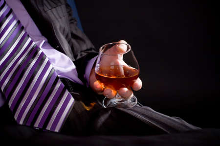 Businessman in formal dress relax with glass of cognac over black background. Image with copyspace. Focus on hand with glass. photo