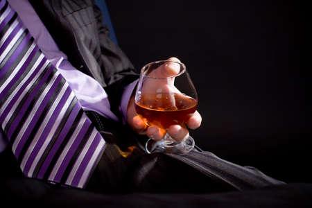 whiskey: Zaken man in formele jurk relax met glas cognac via een zwarte achtergrond. Afbeelding met copyspace. Enerzijds gericht met glas.