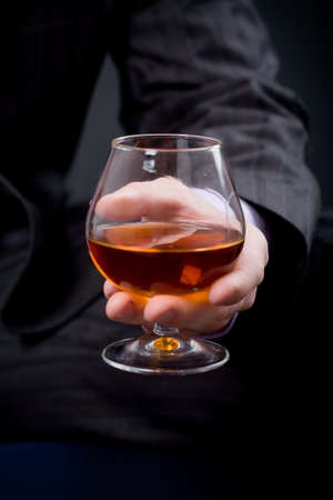 Hand with glass of cognac over black background. Focus on hand with glass. photo