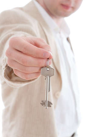 Businessman holding the keys of new house. Focused on the key and the hand only, the rest is blur. photo