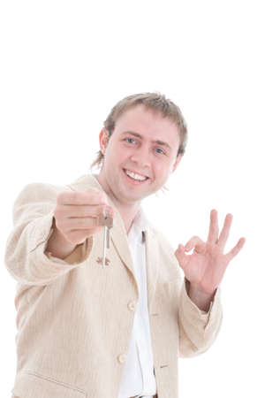 hypothec: Businessman holding the keys of new house and show OK sign. Focused on the face, the keys is blur.