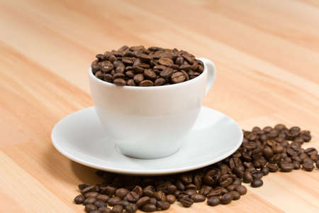energize: Cup with freshly roasted coffee beans on hardwood floor or on the table Stock Photo