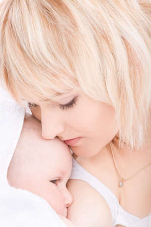 feeding: Mother kiss and breast feeding her baby girl Stock Photo