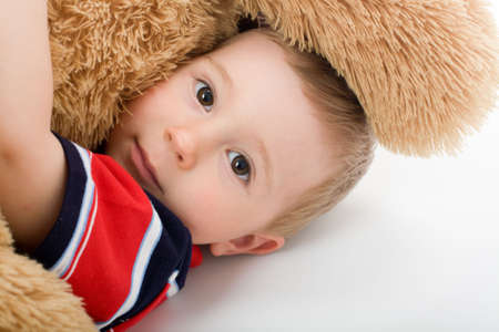 Little boy lye on white bed and embrace toy bear photo