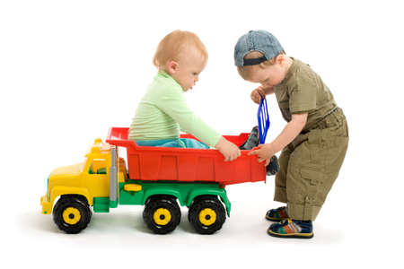 Two little boys play with toy truck. One boy sit on the car and second boy repair the cars body