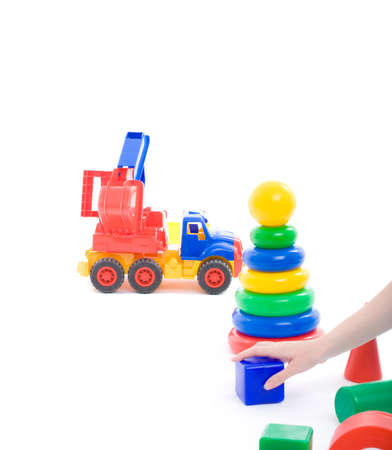 Mothers hand put cube on floor and invite baby to play with toys on playground. Image with copyspace isolated on white with light shadows photo