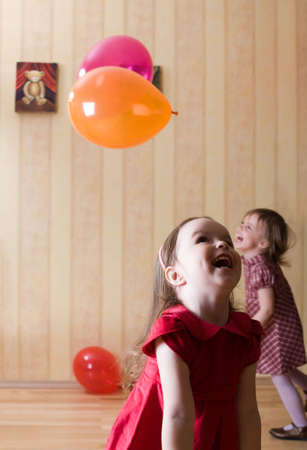 hilarity: Portrait of two little girls playing with airy balls at home