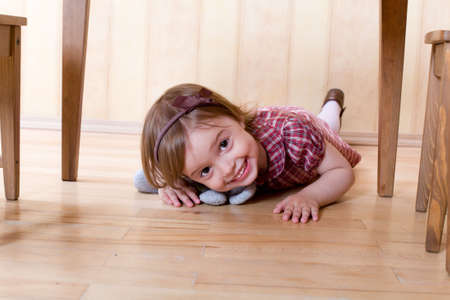 Happy little girl with toy on the hardwood floor crawling under table