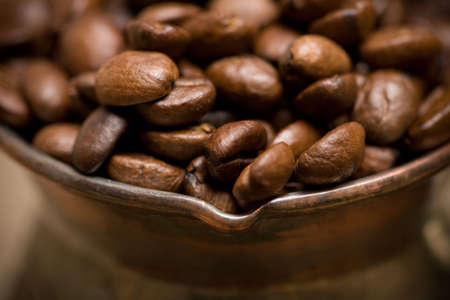 cezve: Cezve with freshly roasted coffee beans on sackcloth. Shallow depth of field. Focus on center of image Stock Photo