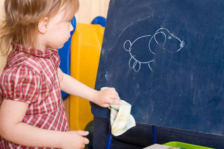 shred: Little girl wipe drawing on a slate tablet. Focus on the tablet.