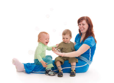 Young mother with her sons enjoy with coloured soap bubbles over white background photo