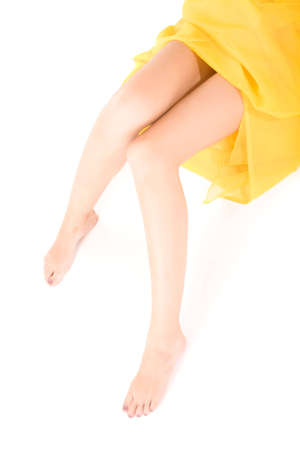 Long legs of relaxing lady covered by yellow cloth over white photo