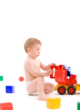 Little boy play with toys over white background with light shadows. photo