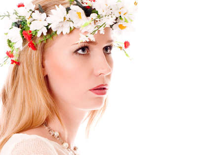 Pretty spring girl with wreath on head looking forward on white background photo
