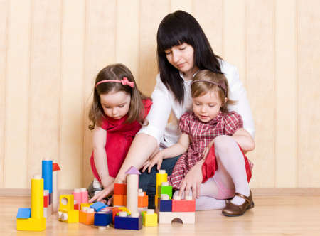 Mother and daughters play with bright geometric toys at home photo
