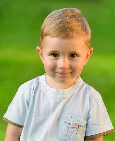 Portrait of little boy on sunny green grass field photo