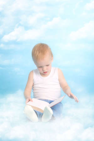 Heaven book. Two years old cute boy reading a book in the cloud sky photo