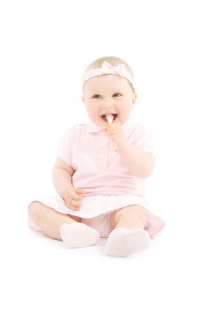 comfit: Sweet happy little girl tasting sugar candy on stick. Over white background