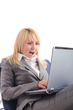 Amazed businesswoman with laptop in chair over white background Фото со стока