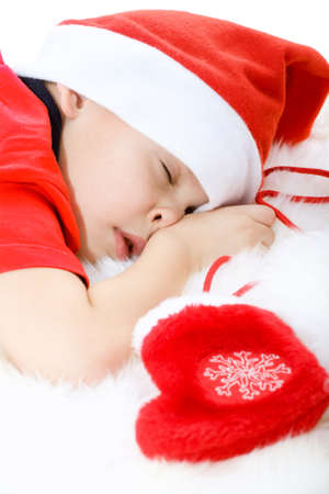 Little boy in Santas hat sleeping and clench ones fist with christmas sock. Upper part of image isolated photo