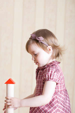 Portrait of a little girl building toy tower from wooden bricks at home photo