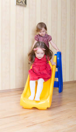 babysit: Two adorable girls having fun atop playground slide at living room Stock Photo