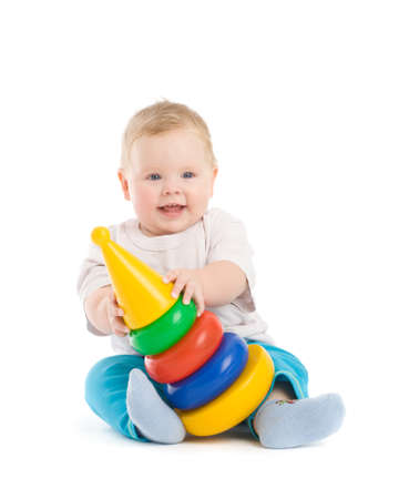 Baby play with tower from colorful discs. Image isolated on white with light shadows