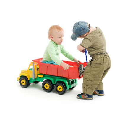 Two little boys play with toy truck. One boy sit on the car and second boy repair the cars body photo