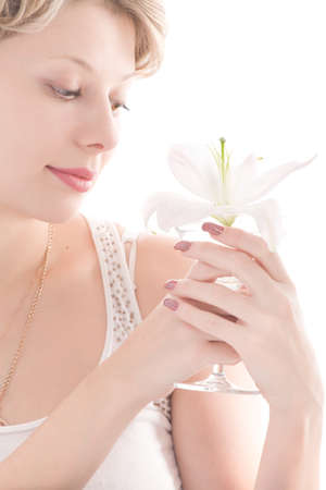 Portrait of attractive blond girl smelling white lily over white background photo