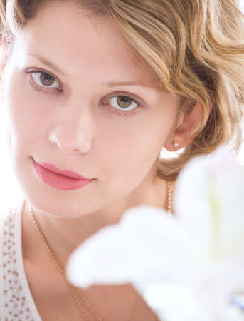 Portrait of attractive blond girl with white lily over white background photo