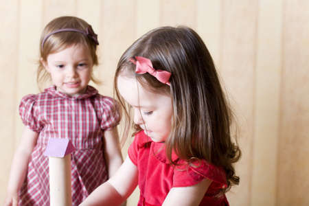 Portrait of two little girls building toy tower from wooden bricks at home photo