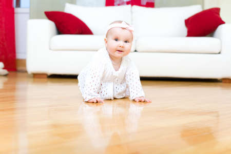 Happy eight month old baby girl crawling on a hardwood floor in living room photo