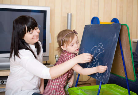 Mother teaching her daughter drawing sketches on blackboard. Prepare to school series. Stock Photo - 4303415